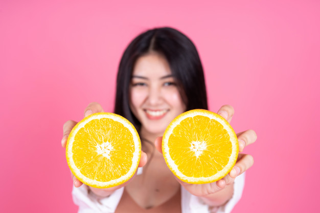щастливо момие, което държи две половинки на портокал, които могат да бъдат използвани в смути